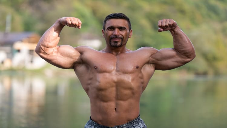 A bodybuilder flexing his muscles outside