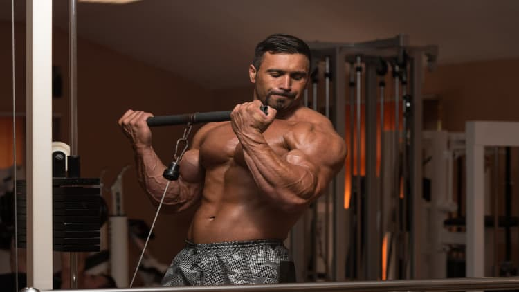 A bodybuilder doing low cable curls for his biceps