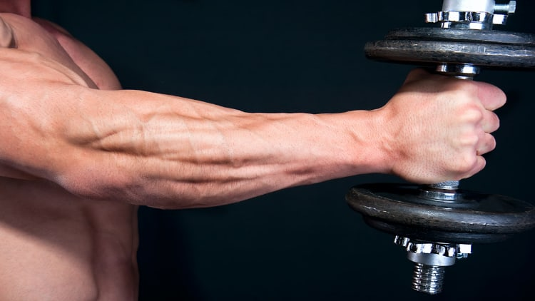 A close up of a bodybuilder's forearm and hand holding a dumbbell
