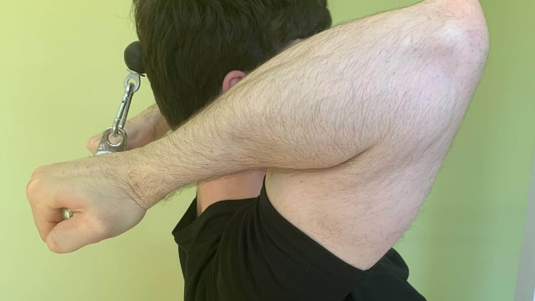 A man performing the cable behind the neck curl exercise for his biceps