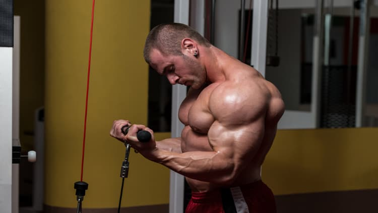Bodybuilder doing a standing cable bicep curl