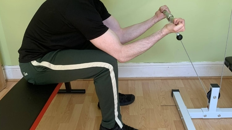 Man performing a cable concentration bicep curl