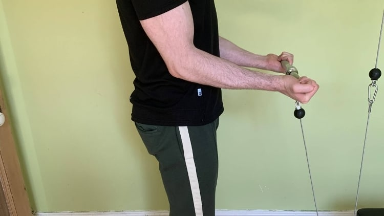 Man performing cable straight bar curls for his biceps