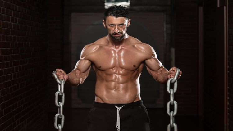 Fitness model doing bicep curls with chains