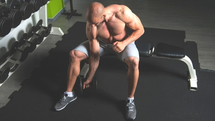 A muscular man doing DB concentration curls for his biceps
