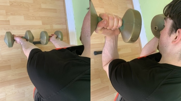 Man performing a dumbbell spider curl for his biceps on an incline bench
