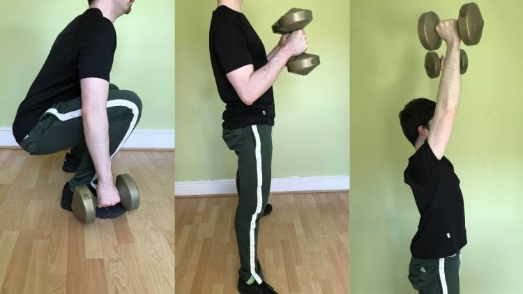 Man performing a dumbbell squat curl press exercise