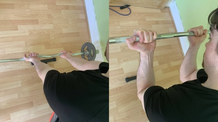 A man doing EZ bar spider curls for his biceps