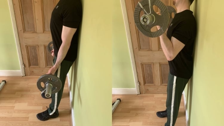 A man performing an EZ bar wall curl for his biceps