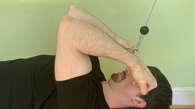 Man performing a guillotine cable curl for his biceps