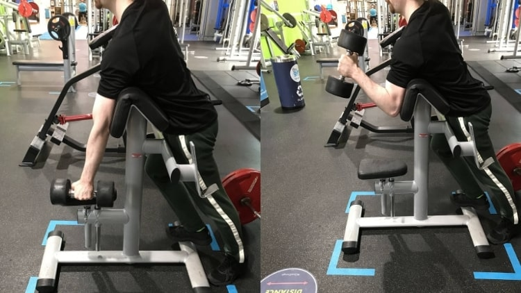 A man performing a hammer spider curl at the gym