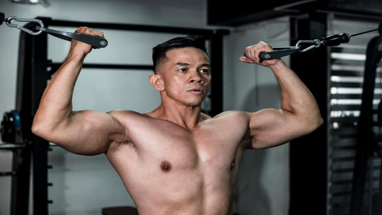 Man doing double bicep cable curls