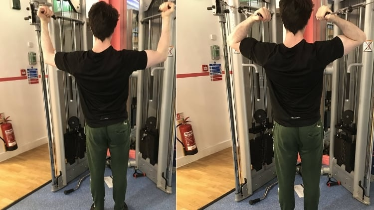 A man doing high pulley cable curls