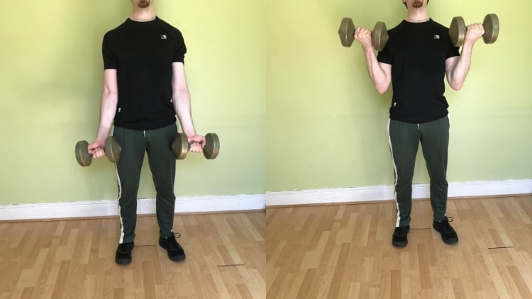 A man showing how to do bicep curls with dumbbells in a standing position