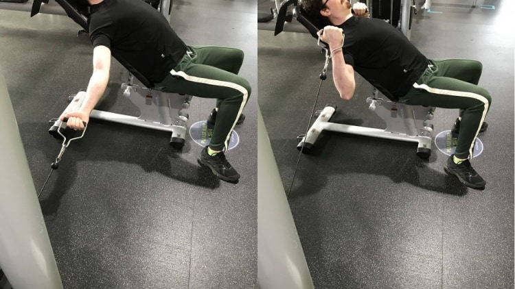 A man performing incline cable curls at the gym