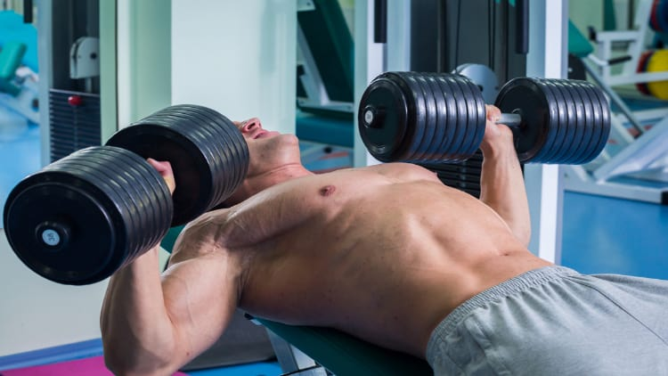 Man performing a heavy incline dumbbell bench press at the gym