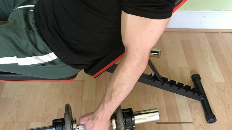 A man performing incline dumbbell hammer curls