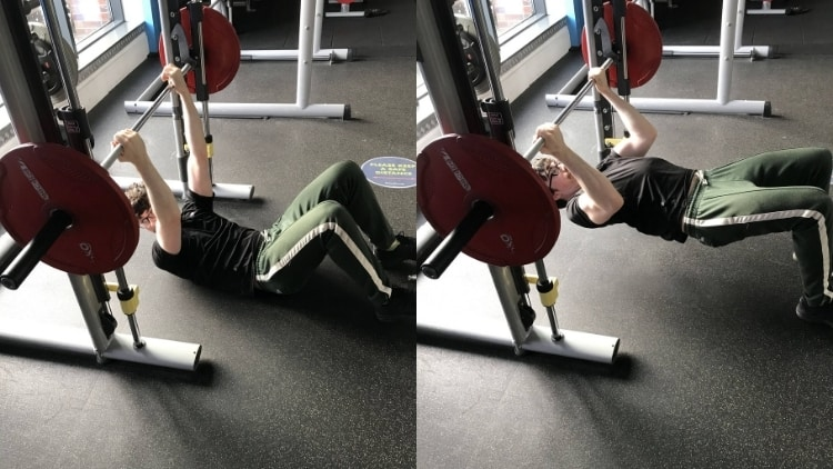 A man performing inverted bicep curls at the gym