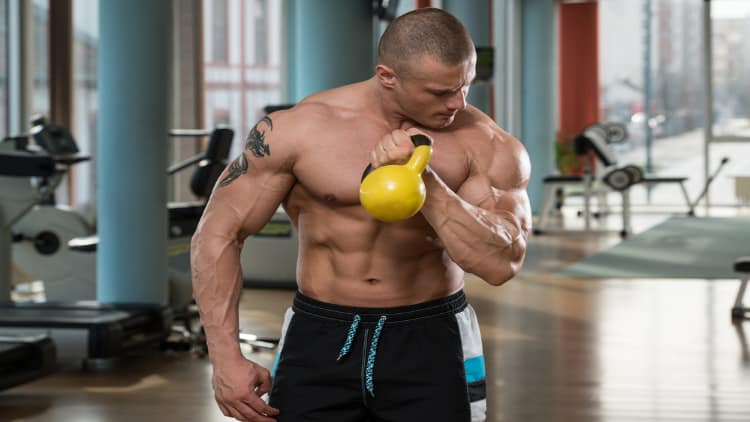 Bodybuilder doing a kettlebell bicep curl at the gym