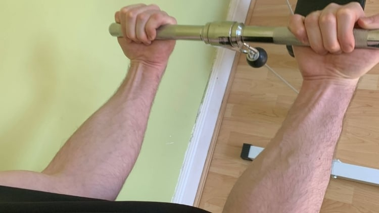 Man holding the bar for low cable curls