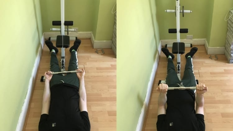 A man performing a lying bicep cable curl