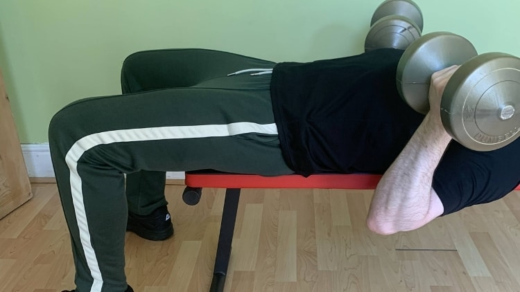 Man doing a lying dumbbell curl for his biceps