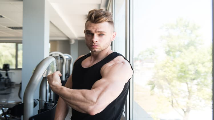 Young muscular man flexing his arm in the gym