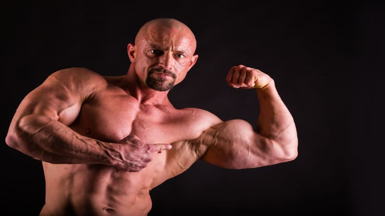 Man pointing to his flexed bicep