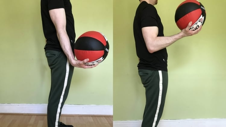 A man doing medicine ball curls for his biceps