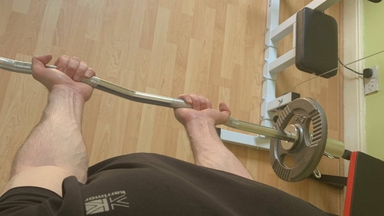 A man doing a narrow grip EZ bar curl