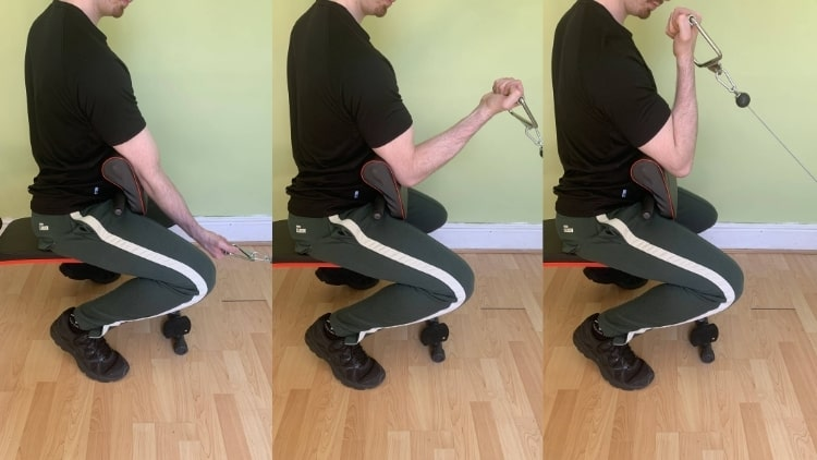 A man performing a one arm cable preacher curl