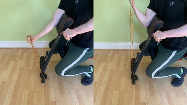 A man performing a one arm resistance band preacher curl