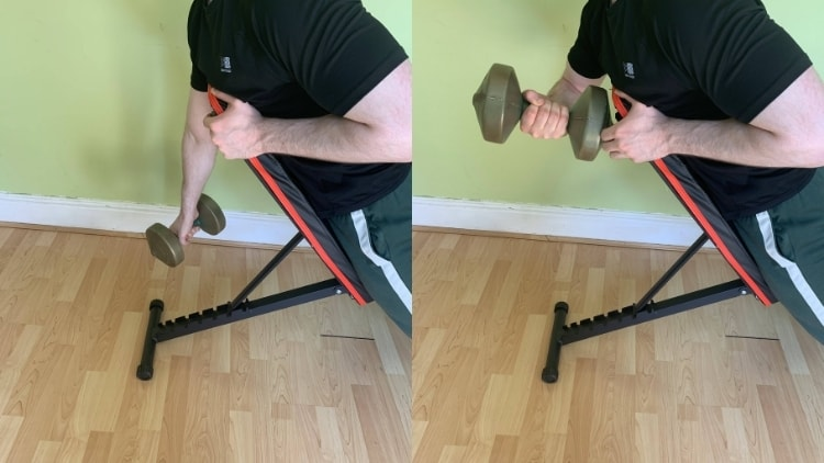 A man performing a one arm spider curl with a dumbbell