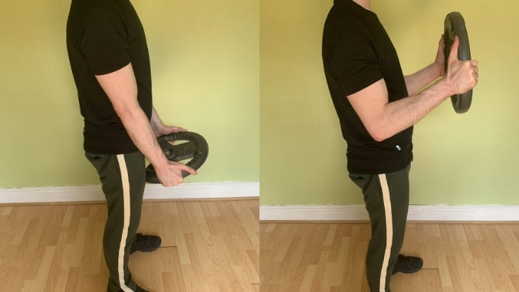 A man performing the plate bicep curl exercise