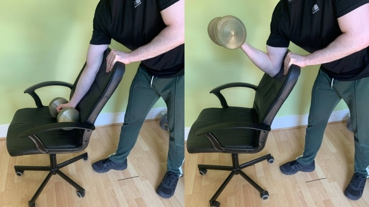 A man doing a preacher curl at home without a bench