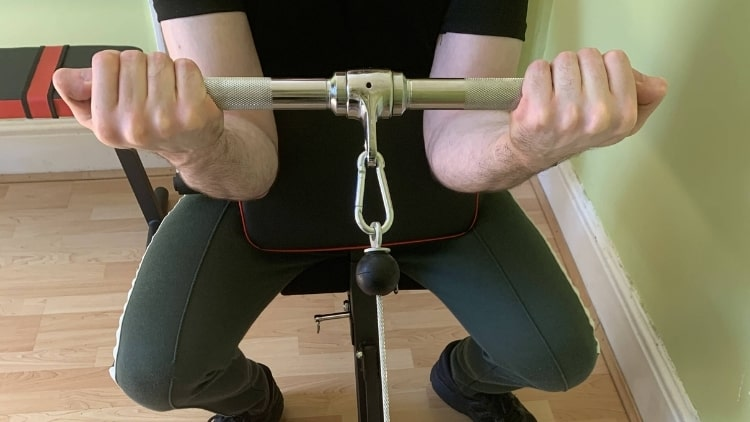 A man doing a preacher curl with cables