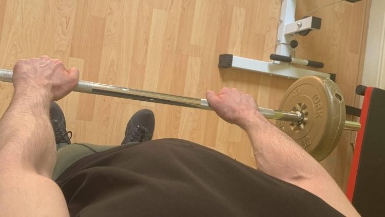 Man performing reverse grip barbell curls