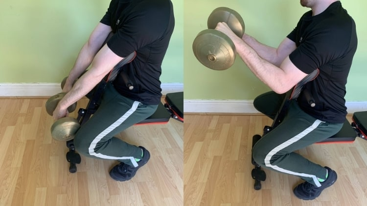 A man performing a reverse preacher curl with dumbbells