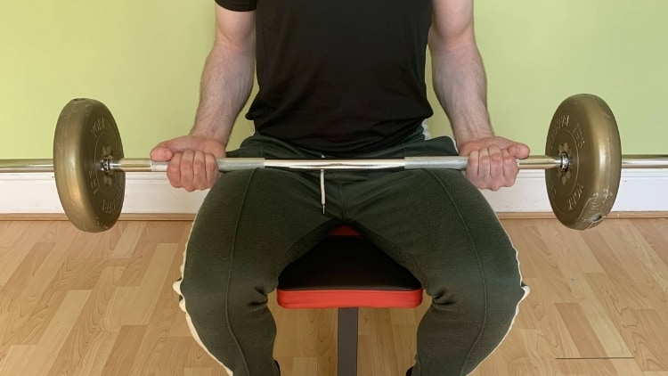 Man performing a seated barbell biceps curl