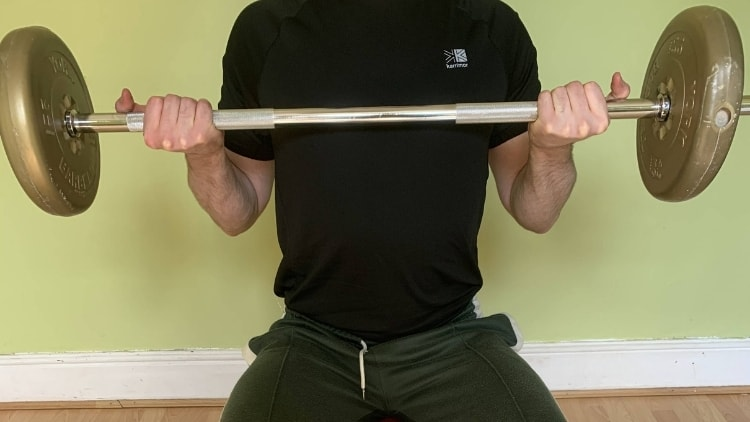Man performing seated barbell curls for his biceps