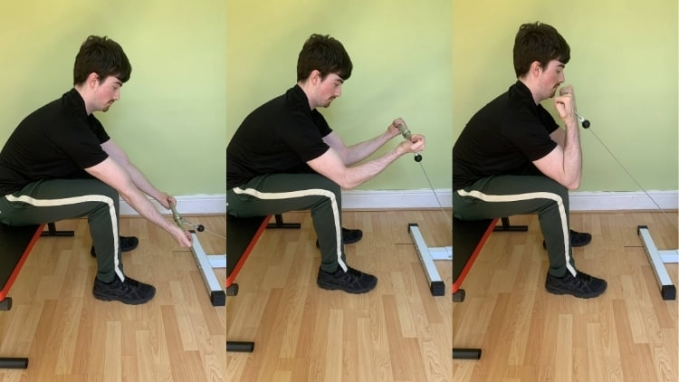 Man performing seated cable curls for his biceps