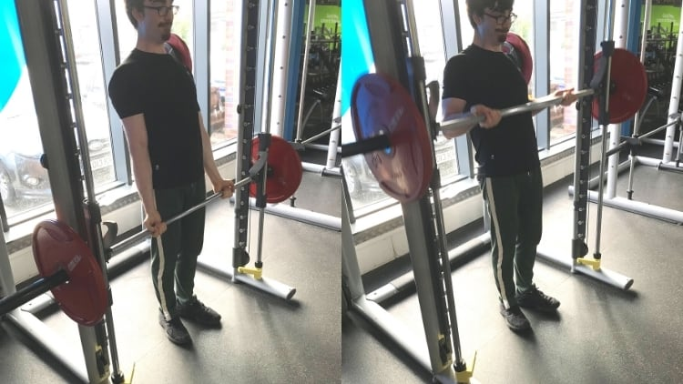 A man performing Smith machine drag curls for his biceps