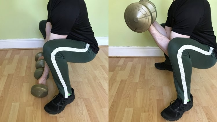 A man doing a squat curl for his biceps