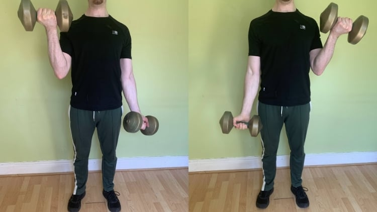 A man performing standing alternating dumbbell curls for his biceps