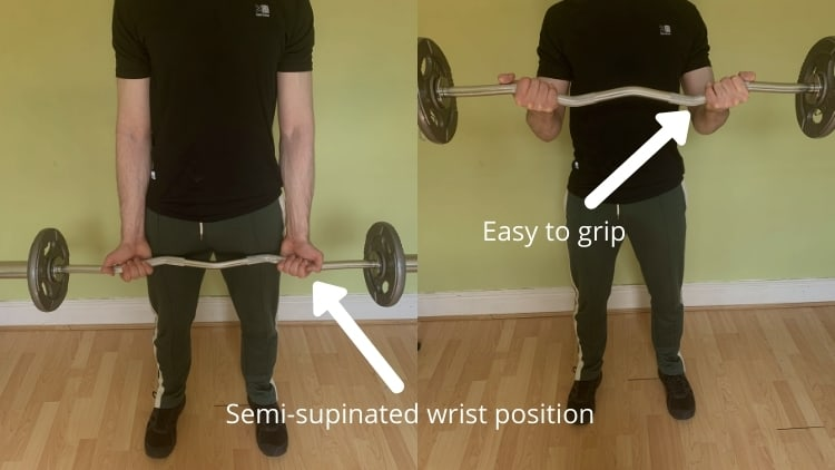A man performing a standing cambered bar curl