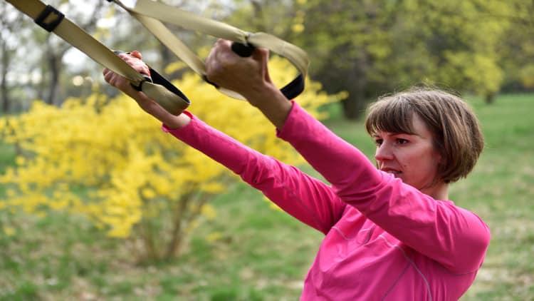 Woman performing TRX bicep exercises