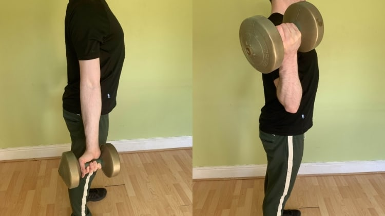 A man doing wide dumbbell curls for his biceps