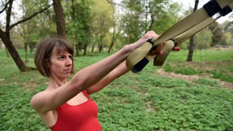 A woman using her TRX outside