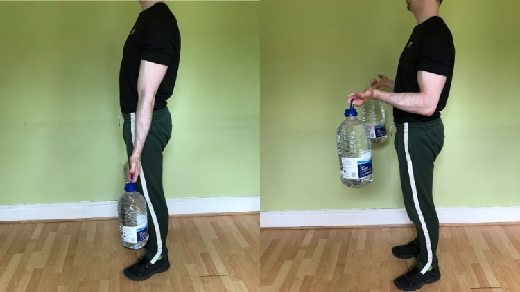 A man doing bicep curls without weights - using water bottles
