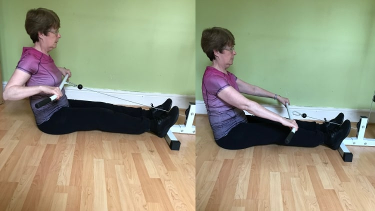 A woman performing a cable row for her back